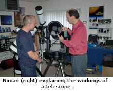 ninian explaining, to a customer, how a telescope works